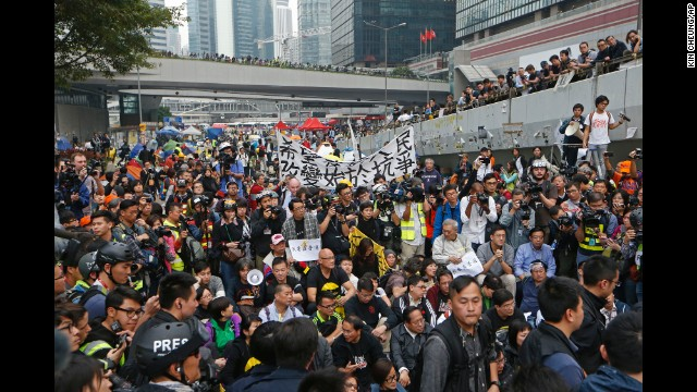 Protesters attend a sit-in rally as police officers break down the campsite.