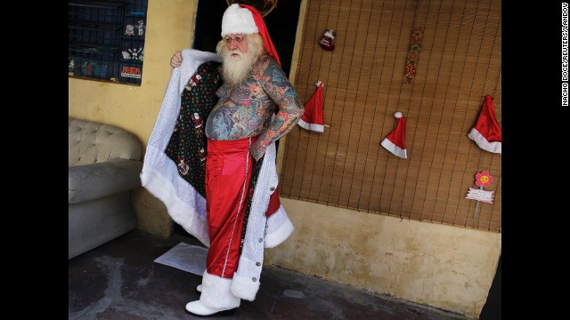 <strong>December 7:</strong> Vitor Martins puts on his Santa Claus outfit before performing in the town square of Sao Caetano do Sul, Brazil. Tattoos cover 94% of Martins' body. Several of them are in reference to Christmas.