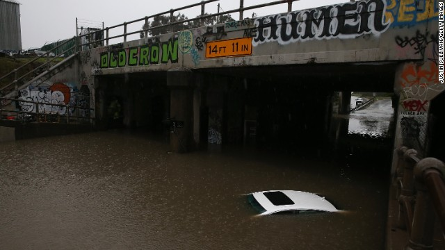 Only the roof of a car is left visible as it sits underwater in a flooded section of Ashby Avenue on December 11 in Berkeley, California.