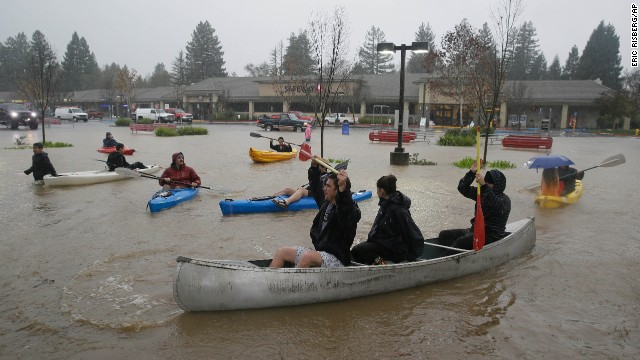 People in kayaks and a canoe make their way around a flooded parking lot at a shopping center on Thursday, December 11, in Healdsburg, California.