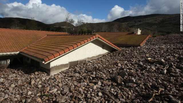 Homes are covered with rocks and mud after debris flows smashed into houses on December 12, in Camarilla, California.