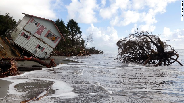A two-story house leaning over the eroding ocean shoreline of North Cove, Washington, is seen on Friday, December 12, as the tide rises.