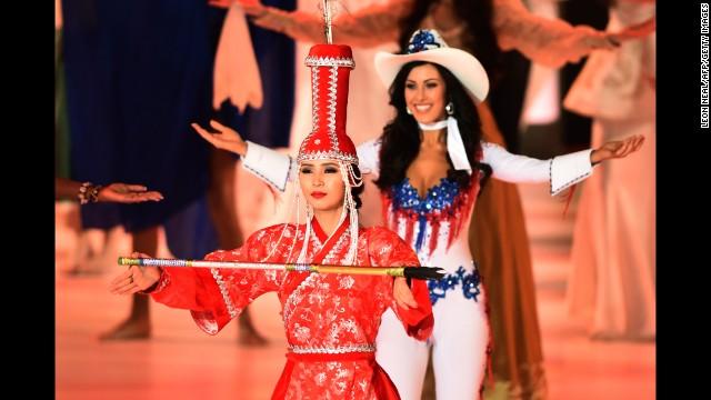 Miss Mongolia Battsetseg Turbat dances with other contestants on stage.