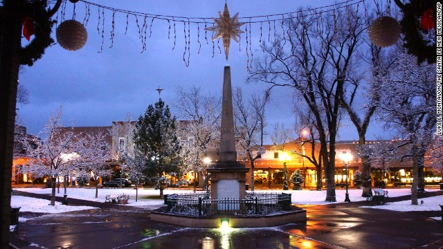The plaza in Santa Fe, New Mexico, is blanketed with snow on Sunday, December 14, following snow showers from a storm system that slammed California and moved into the area. A powerful storm that has been lashing Northern California has moved southward as weather systems whip rain and snow at the West Coast and inland areas.