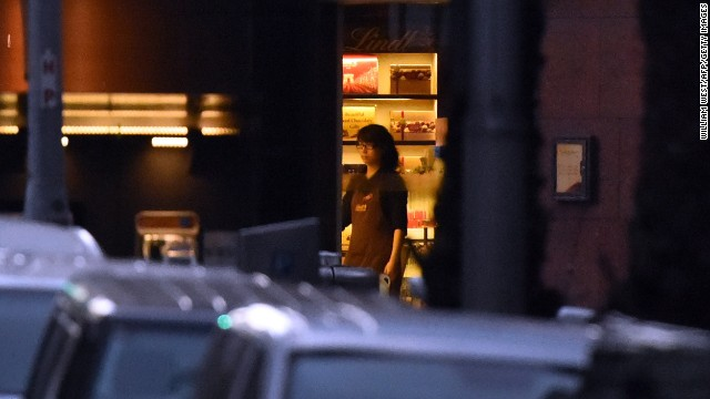 A hostage stands by the front entrance of the cafe as she turns off the lights on Monday, December 15.