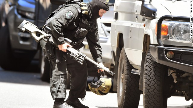 A police sniper walks to his vehicle during a hostage siege in the central business district of Sydney, December 15.