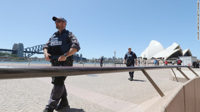 Armed police patrol near the Sydney Opera House. Major landmarks in Sydney were evacuated as police responded to the hostage situation.
