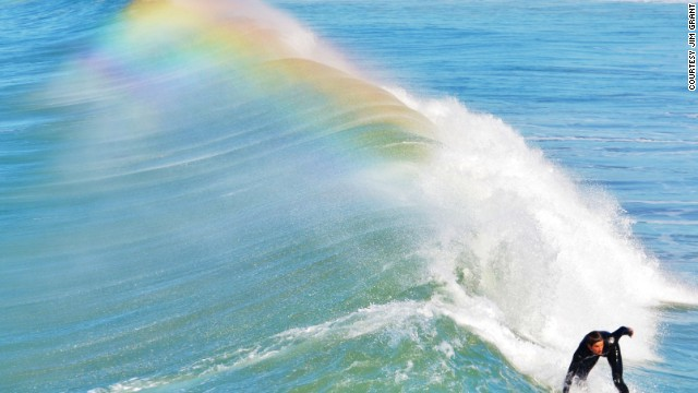 A surfer rides a wave off the coast of San Diego, California.