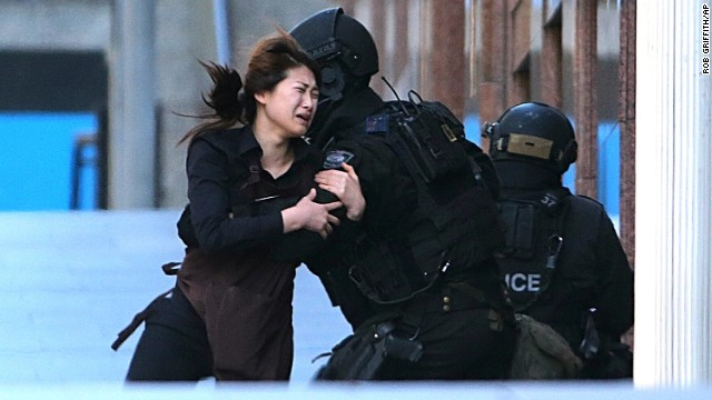 <strong>December 15:</strong> A woman runs to police officers after she escaped <a href='http://www.cnn.com/2014/12/14/world/gallery/sydney-police-operation/index.html' target='_blank'>a hostage situation at a Sydney cafe</a>. The siege ended with the death of the gunman and two of his hostages, but <a href='http://www.cnn.com/2014/12/16/world/asia/australia-sydney-cafe-siege-questions/index.html' target='_blank'>questions remain unanswered.</a>