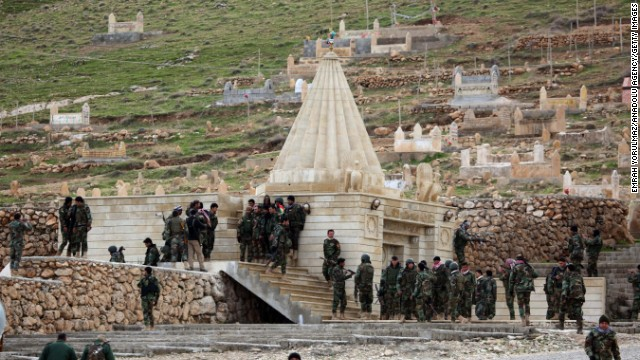 """Kurdish Peshmerga fighters assemble at a shrine on Iraq's Mount Sinjar on Friday, December 19. The Kurdish military said that with the help of coalition airstrikes, it has """"cleansed"""" the area of ISIS militants. ISIS has been advancing in Iraq and Syria as it seeks to create an Islamic caliphate in the region."""