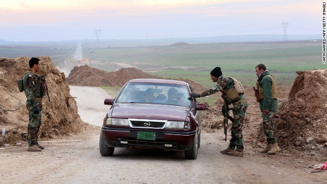 Peshmerga fighters stop to check a vehicle in Zummar on December 18 as they continue to battle ISIS fighters near the border with Syria.