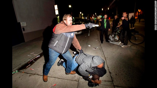 <strong>December 10:</strong> A plainclothes detective from the California Highway Patrol aims his gun at anti-police demonstrators during an arrest in Oakland, California.