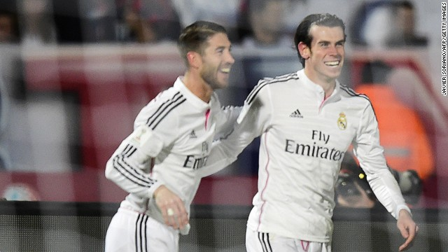 But the smiles are soon back for Real Madrid when Gareth Bale (right) scores a second goal against San Lorenzo.