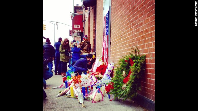 "NEW YORK: ""In Brooklyn a memorial grows to the two murdered NYPD officers."" CNN's Martin Savidge <a href='http://instagram.com/martinsavidge' target='_blank'>@martinsavidge</a>, December 21. The two police officers were killed execution style Saturday afternoon as they sat in their marked police car on a Brooklyn street corner. The gunman was found dead in a nearby subway station from a self-inflicted gunshot wound. So far, police have not commented on the motive for the Brooklyn shootings, except to say the officers were not engaging the shooter in any way when they were shot."