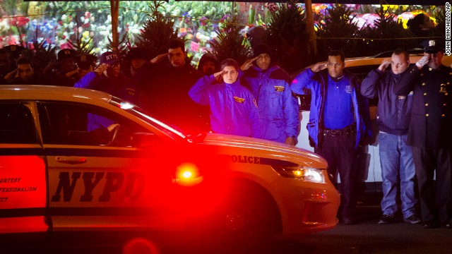 Mourners stand at attention as the bodies of two fallen NYPD officers are transported from Woodhull Medical Center on Saturday, December 20.