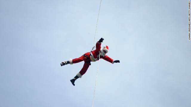 Firefighter Hector Chaco maneuvers down a cable from a bridge to deliver presents to children as Santa on December 21 in Guatemala City.