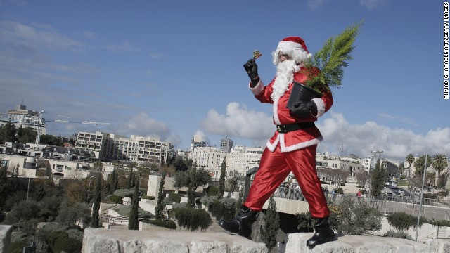A Palestinian dressed as Santa Claus distributes Christmas trees on Monday, December 22, along the wall of Jerusalem's Old City. Check out other images of the jolly old man from around the world as Christmas Day nears: