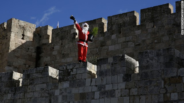 A Palestinian in his Santa duds waves to passers-by as he walks along Jerusalem's Old City walls on December 22.