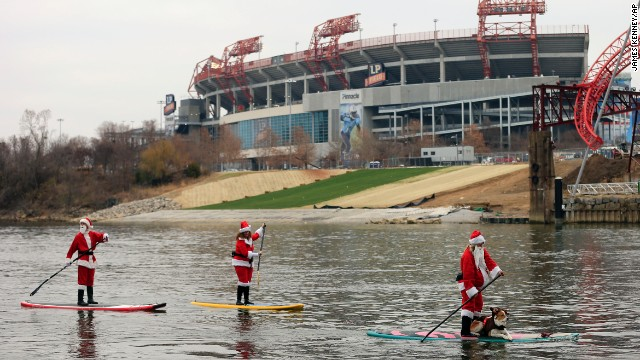 People donning Santa costumes paddle on the Cumberland River near LP Field in Nashville before an NFL football game Sunday, December 14, between the Tennessee Titans and New York Jets.