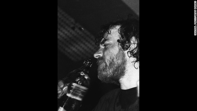 Cocker takes a swig of whiskey during a performance while on tour in Australia. His career nearly derailed over his use of drugs and alcohol in the 1970s.