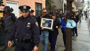 Visitors pay respects to two slain police officers this week at a memorial in New York\'s Bedford-Stuyvesant neighborhood.