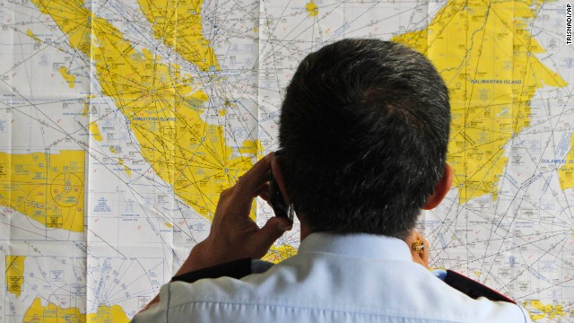 An airport official checks a map of Indonesia at the crisis center for the missing flight, set up by local authorities at Juanda International Airport.