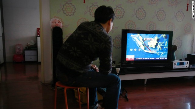 Jiang Hui, whose relatives were on board Malaysia Airlines Flight 370, which went missing on March 8, watches the news about the missing AirAsia flight at his house in Beijing.