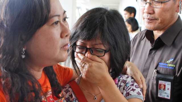 A relative weeps as she waits for the latest news on the missing jetliner.