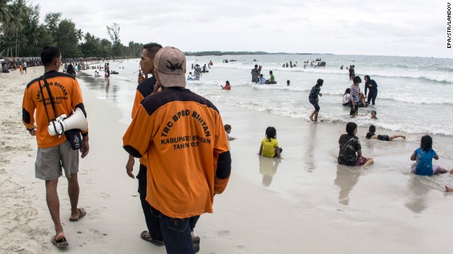 Members of the Indonesian Regional Disaster Management Agency walk at a beach as they search for the missing plane.