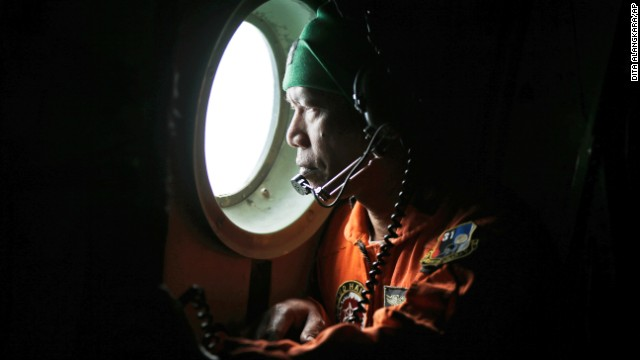 An Indonesian military airman looks out the window of an airplane during a search over the waters of Karimata Strait on Monday, December 29.
