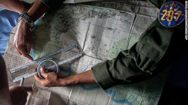 Indonesian Army personnel read a map during a search operation on December 29.