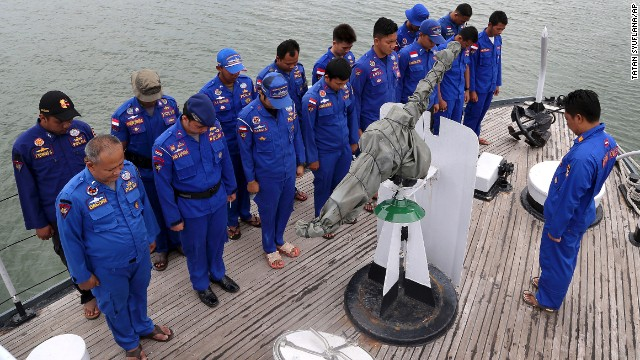 Members of Indonesia's Marine Police pray before a search operation for the missing jet on December 29.