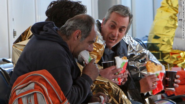 Passengers eat after their arrival at the airport of Corfu island in Greece on December 29.