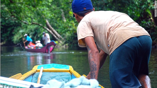 Borneo's Iban people are master boatmen who serve as guides on orangutan tracking expeditions, navigating the Batang Ai River in their shallow-hulled longboats.
