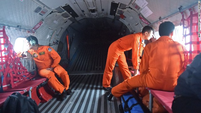 Indonesian air force personnel scan the sea from plane windows during the search.
