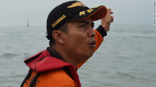 A member of an Indonesian search and rescue team gestures as the team is ferried out to a ship to conduct search operations on December 30.