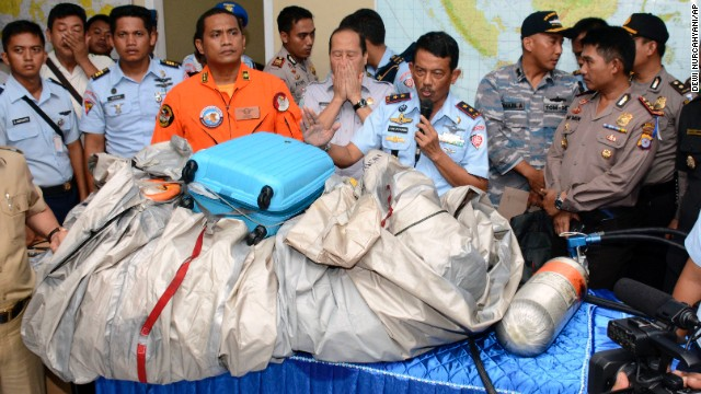 Indonesian Air Force personnel on Tuesday, December 30, show debris, including a suitcase, that was found floating near the site where AirAsia Flight QZ8501 disappeared on Sunday.