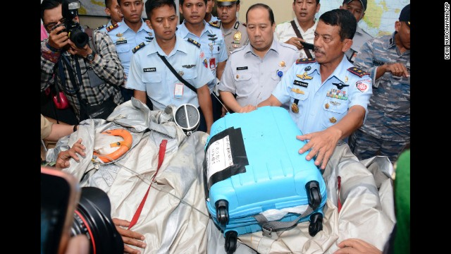 At a press conference Tuesday, December 30, Indonesian air force personnel show airplane parts and a suitcase found floating in the Java Sea near the crash site of AirAsia Flight QZ8501. The Airbus A320-200 lost contact with air traffic control early Sunday, December 28, shortly after the pilot requested permission to turn and climb to a higher altitude because of bad weather, according to Indonesian officials.