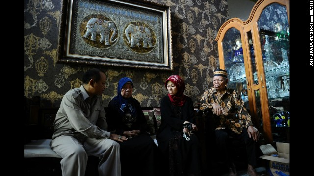 Relatives of the flight's pilot, Captain Iriyanto, gather at his house in Surabaya on December 30. Second from right is his wife, Rr. Widiya Sukati Putri.