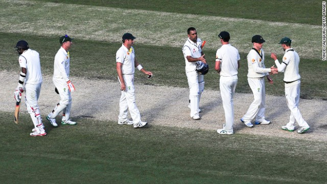 Dhoni (center) shakes hands with Australian cricketers following the draw at the Melbourne Cricket Ground on Tuesday. The result handed the home side an unassailable lead in the four-match series.