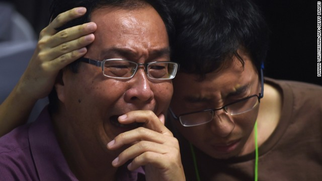 "Relatives at Juanda International Airport in Surabaya comfort each other after hearing officials say they're ""95% sure"" debris is from missing AirAsia flight QZ8501."
