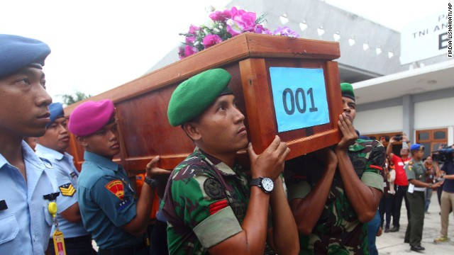 Indonesian soldiers carry a coffin containing a victim of AirAsia Flight QZ8501 upon arrival at an air force base in Surabaya, Indonesia, on Wednesday, December 31.