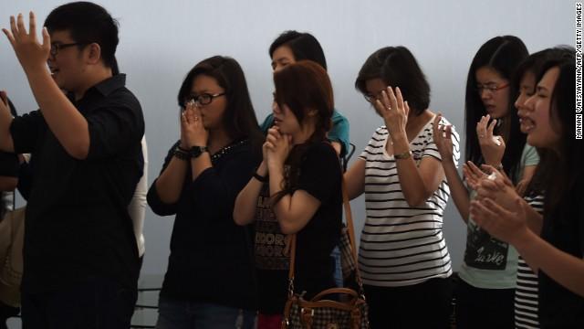 Relatives of passengers pray together inside a holding room at Juanda International Airport in Surabaya on December 31.