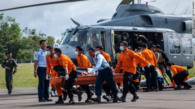 Members of a search and rescue team carry the body of a victim of AirAsia Flight QZ8501 at Iskandar Airbase in Pangkalan Bun, Indonesia, on Thursday, January 1. A massive recovery operation has begun following confirmation from Indonesian officials that remains and debris found in waters off Borneo were from the missing plane.