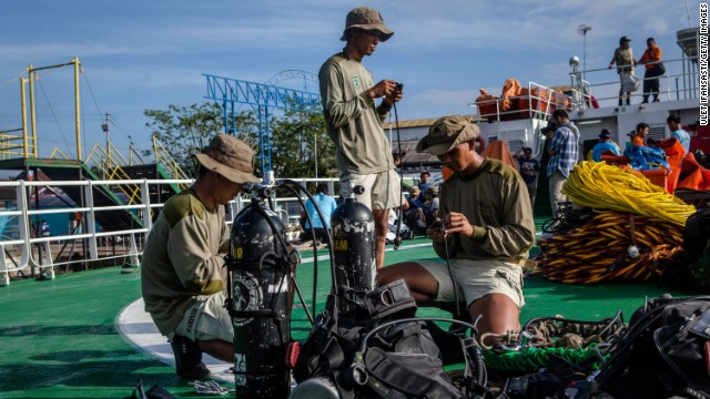 Marine divers prepare their gear on the deck of a ship before searching for passengers and debris from AirAsia Flight QZ8501 on January 1 at Kumai port in Pangkalan Bun.