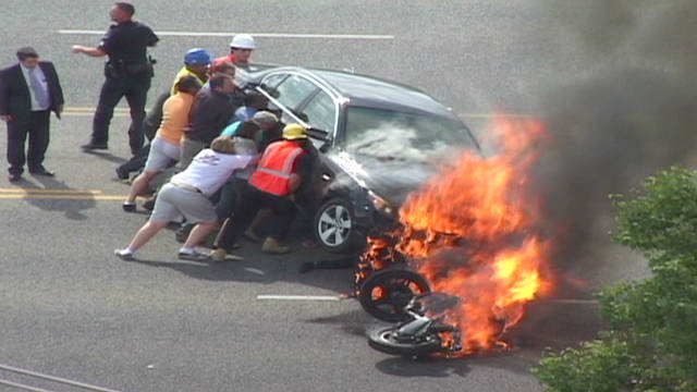 Bystanders lift burning car, save biker