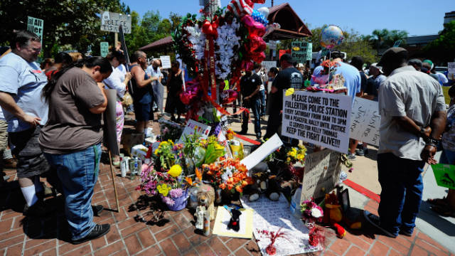 Demonstrators hold a moment of silence at a makeshift memorial for Kelly Thomas, a homeless man who died after an altercation with several officers, during a rally and protest march on August 20, 2011 in Fullerton, California.