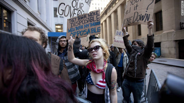 Protesters hold up signs during a demostration near Wall Street on Monday.