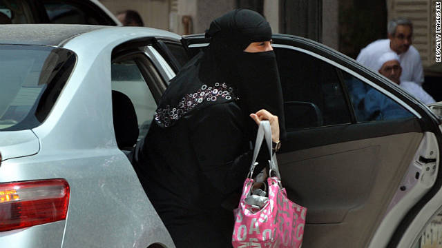 A Saudi woman gets out of the backseat of a car. Religious interpretations do not allow women to drive in Saudi Arabia.