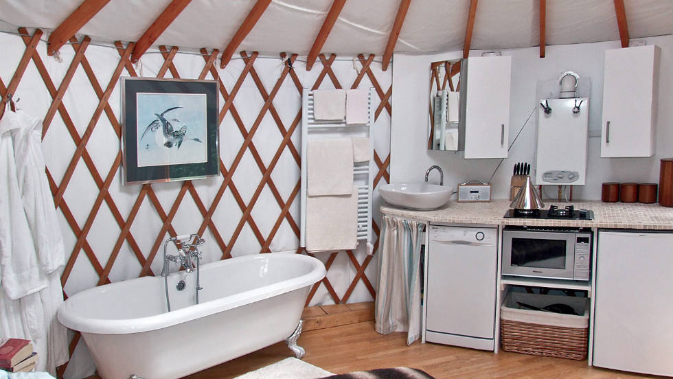Within the yurt there's a kitchen with a dishwasher, a clawfoot tub, a dining area and a bed.
